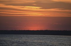Puesta del sol en la orilla El sol ocultó detrás de la orilla opuesta Tarde del verano fotografía de archivo libre de regalías