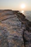 Puesta del sol en la orilla rocosa Imágenes de archivo libres de regalías