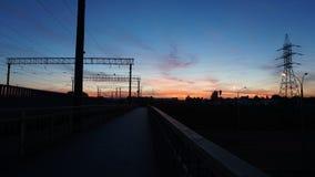 Puesta del sol en la parada del tren con el cielo azul profundo hermoso y las nubes rojas wide fotografía de archivo libre de regalías