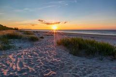 Puesta del sol en la playa arenosa Imagen de archivo libre de regalías