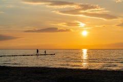 Puesta del sol en la playa con dos personas como siluetas negras en el primero plano fotografía de archivo libre de regalías