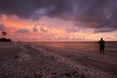 Puesta del sol en la playa con la pesca de la persona Fotografía de archivo libre de regalías