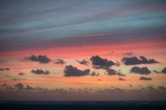 Puesta del sol en la playa con las nubes hermosas Foto de archivo