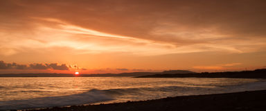 Puesta del sol en la playa con un cielo retroiluminado hermoso Fotografía de archivo libre de regalías