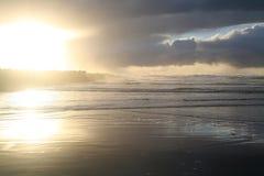 Puesta del sol en la playa con un embarcadero con una tormenta de fractura Imagen de archivo