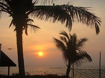 Puesta del sol en la playa de la 'promenade' con los árboles de coco y la choza, Pondicherry, la India Imagenes de archivo