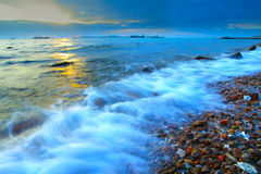 Puesta del sol en la playa de la roca Foto de archivo libre de regalías