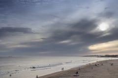 Puesta del sol en la playa de las personas que practica surf Imagen de archivo libre de regalías