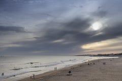 Puesta del sol en la playa de las personas que practica surf Fotografía de archivo