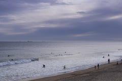 Puesta del sol en la playa de las personas que practica surf Foto de archivo