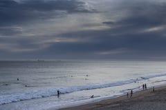 Puesta del sol en la playa de las personas que practica surf Imágenes de archivo libres de regalías