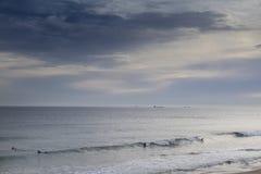 Puesta del sol en la playa de las personas que practica surf Fotos de archivo libres de regalías