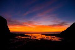 Puesta del sol en la playa de Porth de la capilla, en Cornualles Foto de archivo libre de regalías