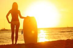 Puesta del sol en la playa del verano con la mujer de la persona que practica surf del cuerpo Imagen de archivo libre de regalías