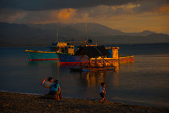 Puesta del sol en la playa La gente se sienta en la playa y mira las naves y el mar Pandan, Panay, Filipinas Fotografía de archivo libre de regalías
