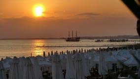 Puesta del sol en la playa, en medio del barco pirata Foto de archivo