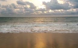 Puesta del sol en la playa nublada imagenes de archivo