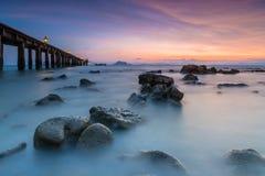 Puesta del sol en la playa rocosa Fotos de archivo libres de regalías
