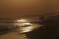 Puesta del sol en la playa, silueta de la gente en Mazagon, Huelva Fotos de archivo