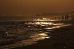 Puesta del sol en la playa, silueta de la gente en Mazagon, Huelva Imagenes de archivo