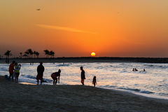 Puesta del sol en la playa Siluetas de la gente contra el contexto del sol poniente Fotografía de archivo libre de regalías