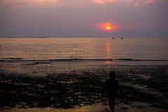 Puesta del sol en la playa y el niño en siluate Imágenes de archivo libres de regalías