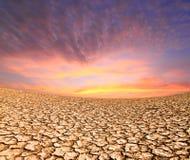 Puesta del sol en la tierra secada por la sequedad fotos de archivo