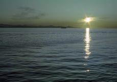 Puesta del sol en las aguas azules del estado de Washington en el noroeste pacífico Foto de archivo