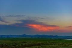 Puesta del sol en las colinas Foto de archivo libre de regalías
