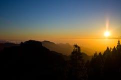 Puesta del sol en las montañas con los árboles Imágenes de archivo libres de regalías