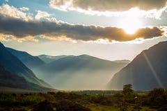 Puesta del sol en las montañas en el valle fotografía de archivo