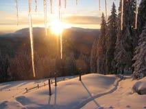 Puesta del sol en las montañas en la ventana helada Imagenes de archivo