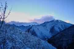 Puesta del sol en las montañas nevosas Imágenes de archivo libres de regalías