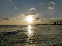 Puesta del sol en las nubes encendido como revestimiento de la onda hacia la playa del océano fotos de archivo