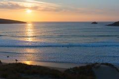 Puesta del sol en las personas que practica surf de Cornualles que practican surf la bahía y la playa Cornualles del norte Inglat Fotografía de archivo libre de regalías