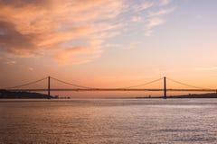 Puesta del sol en los 25 de Abril Bridge, Lisboa, Portugal Imagen de archivo libre de regalías