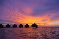 Puesta del sol en los Maldivas con vistas a la laguna y a las casas de planta baja Imágenes de archivo libres de regalías