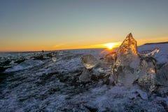 Puesta del sol en los pedazos que brillan intensamente de Diamond Beach In Iceland With del hielo fotografía de archivo