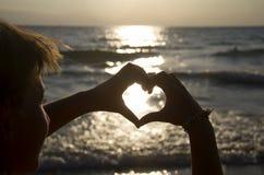 Puesta del sol en manos del corazón Imagen de archivo libre de regalías