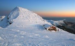Puesta del sol en montañas con el chalet alpestre fotografía de archivo libre de regalías