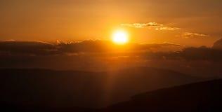 Puesta del sol en montañas con las colinas, cielo colorido, sunlights del eith del sol Foto de archivo libre de regalías