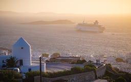Puesta del sol en Mykonos con los molinoes de viento y el barco de cruceros, Grecia Imagen de archivo libre de regalías