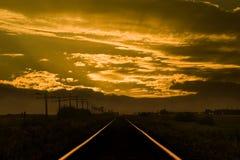 Puesta del sol en pistas del tren Imagen de archivo libre de regalías