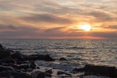 Puesta del sol en tiempo tranquilo en la playa Foto de archivo