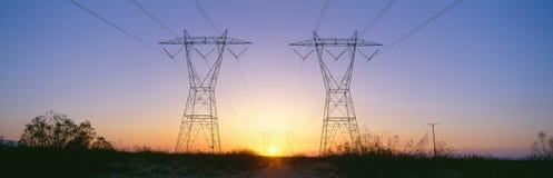 Puesta del sol en torres eléctricas de la transmisión Fotos de archivo libres de regalías