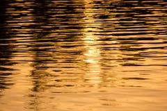 Puesta del sol en un agua fotos de archivo