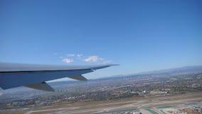 Puesta del sol en un beachPlane que saca de aeropuerto, visión del centro vacacional a través de una ventana del aeroplano