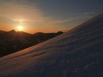 Puesta del sol en un canto alpestre nevoso Imagen de archivo