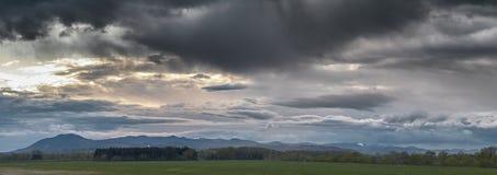 Puesta del sol en un cielo dramático de las nubes sobre un prado y un pequeño bosque del pino con las colinas en fondo, cerca de  imagenes de archivo