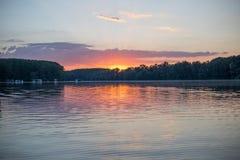 Puesta del sol en un lago con las casas en el agua Foto de archivo